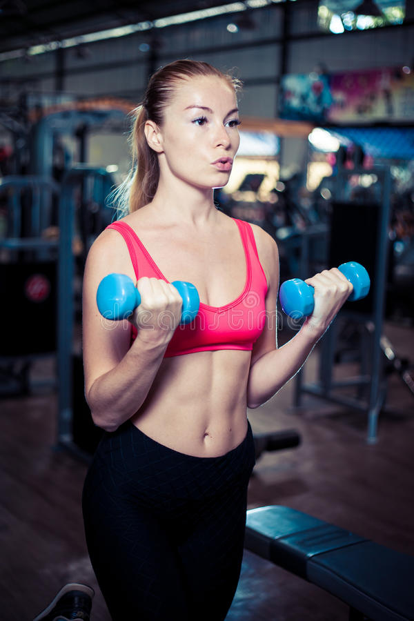 Beautiful fitness girl with dumbbells. Attractive woman in gym. Caucasian blond model with long hair royalty free stock photo