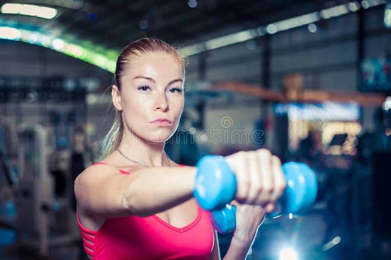 Beautiful fitness girl with dumbbells. Attractive woman in gym. Caucasian blond model with long hair royalty free stock photos