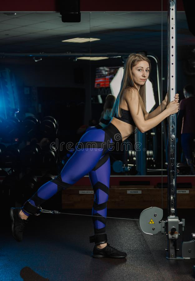 Beautiful fitness model girl trains buttocks leg abduction on the simulator in the gym. stock images