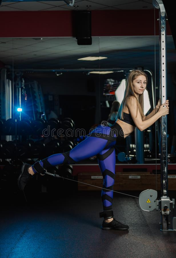 Beautiful fitness model girl trains buttocks leg abduction on the simulator in the gym. stock photography