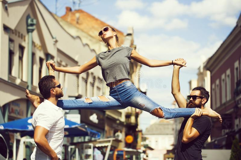 Beautiful fitness sport woman making split leg, handsome men outdoor. Beautiful fitness sport women or young girl in jeans making split leg on hand of handsome royalty free stock image