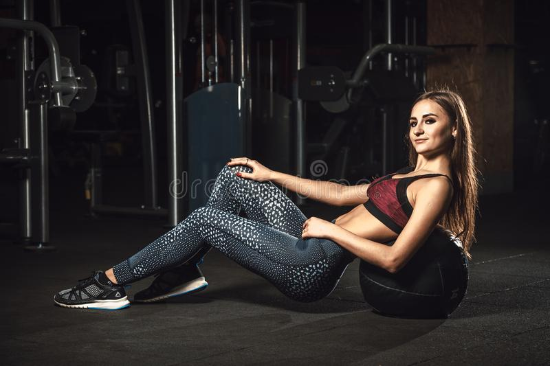 Beautiful fitness sporty young girl lies on the ball flexing abdominal muscles royalty free stock image