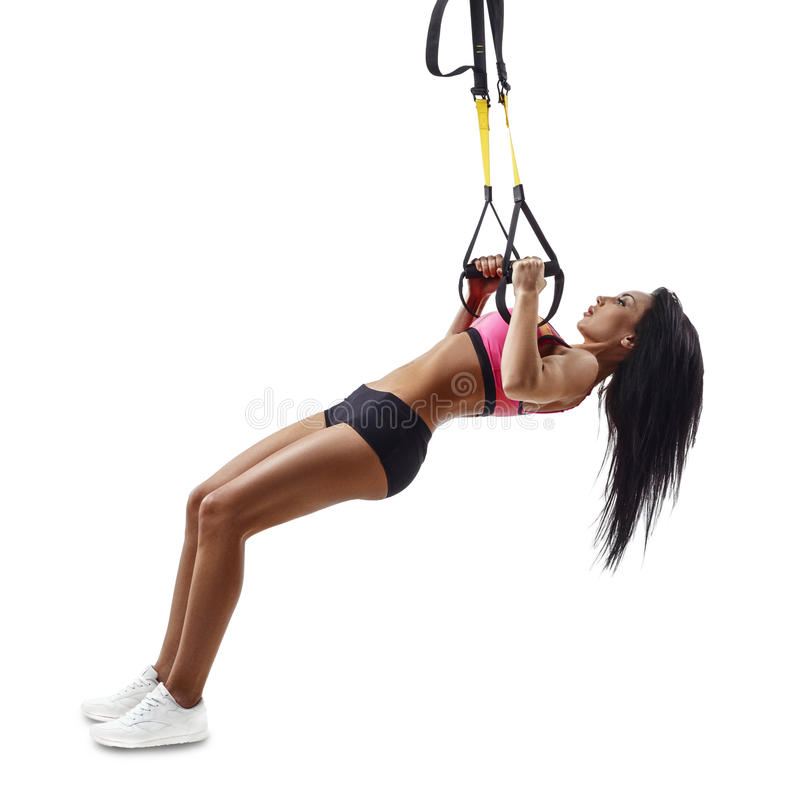 Beautiful fitness woman do Inverted Row with trx suspensions stock image