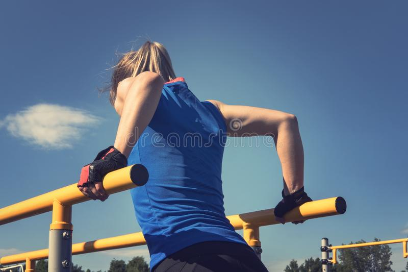 Beautiful fitness woman doing exercise on parallel bars outdoor. royalty free stock photography