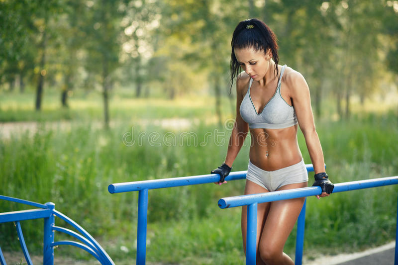 Beautiful fitness woman doing exercise on parallel bars sunny outdoor. Sporty girl doing push ups on bars outdoor royalty free stock photography