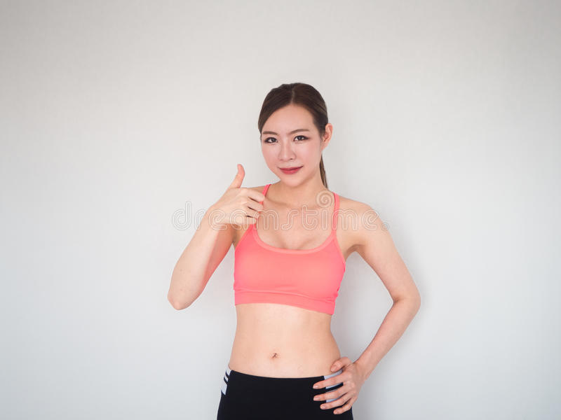 beautiful fitness woman holding thump up sign,sport woman on white background stock photography