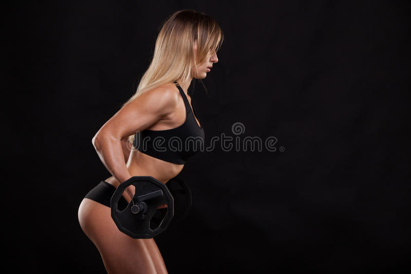 Beautiful fitness woman is lifting a barbell. Sporty girl showing her well trained body. isolated on dark background. With copyspace stock photo
