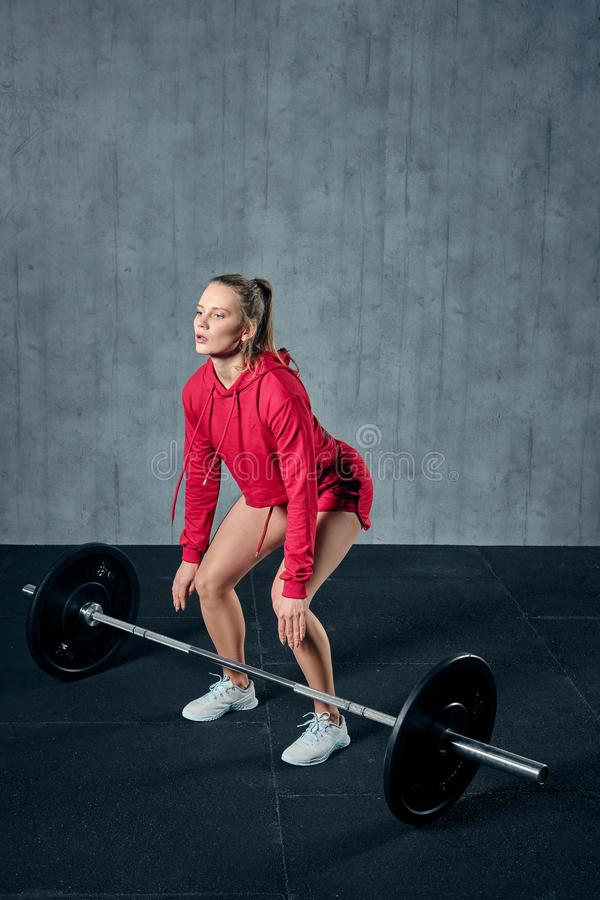 Beautiful fitness woman lifting barbell. Sporty woman lifting weights. Fit girl exercising building muscles. stock photos
