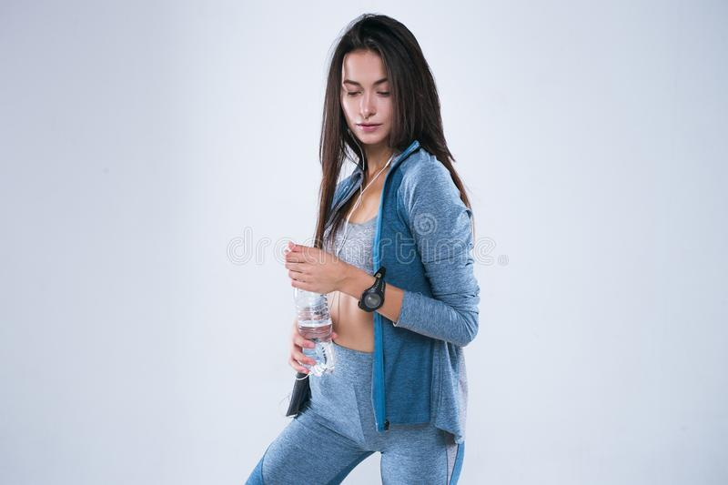 Beautiful fitness woman posed with bottle of water in earphones. Rest after training and drinking water. Beautiful fitness woman posed with bottle of water in stock images