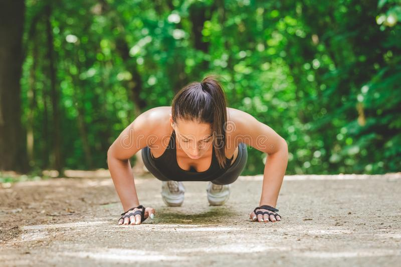Beautiful fitness woman warming up for training by doing push ups outdoors. Sportswoman doing push ups in nature stock photography