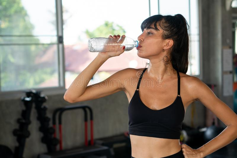 Beautiful fitness young woman tired taking a break from exercise cooling down drinking water bottle  in gym . healthy sport girl royalty free stock photo