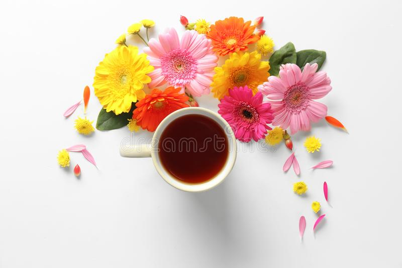Beautiful flat lay composition with cup of tea and flowers on white background royalty free stock photo