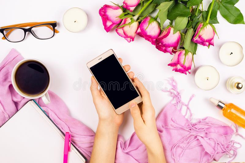 Beautiful flat lay with flowers, cup of tea, candles,glasses and other accessories. Concept of a woman`s workplace, white background stock images