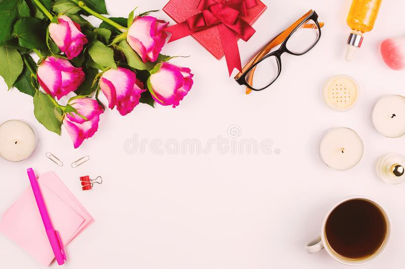 Beautiful flat lay with flowers, cup of tea, glasses, candles and other accessories, concept of a woman`s table. White background. Toned image royalty free stock photos