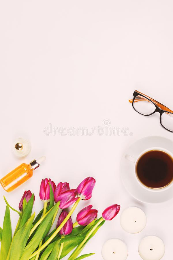 Beautiful flat lay with flowers, cup of tea, glasses, candles and other accessories, concept of a woman`s table. White background. Toned image royalty free stock images