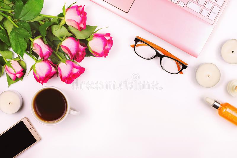 Beautiful flat lay with laptop, flowers, cosmetics, glasses, candles and other accessories royalty free stock photography