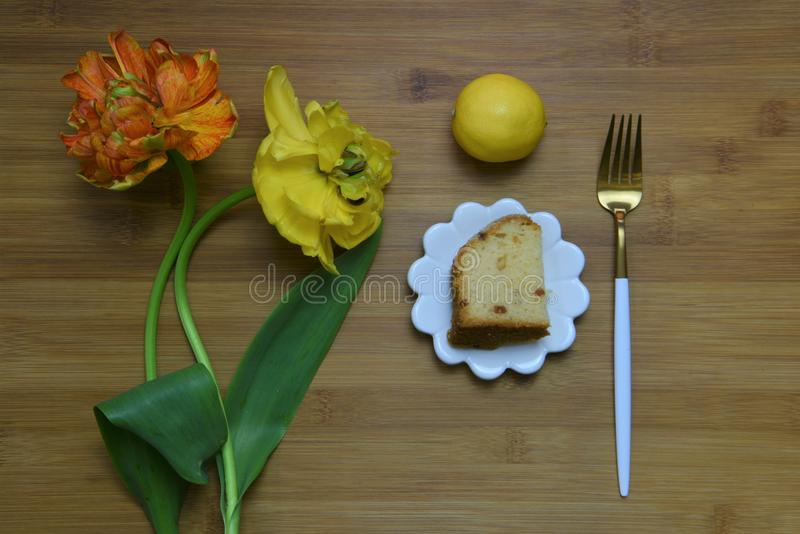 Beautiful flat lay with summer time flowers and lemon cake stock photo