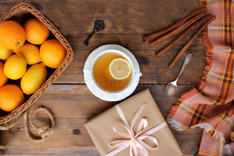 Beautiful flat on an old wooden background, a cup of tea with lemon and cinnamon sticks, candles, a gift in paper, cones, top view royalty free stock image