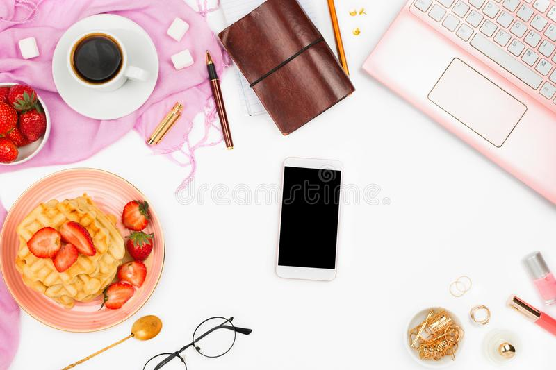 Beautiful flatlay arrangement with cup of coffee, hot waffles with cream and berries, laptop, smartphone with copyspace and other. Accessories: concept of busy stock image