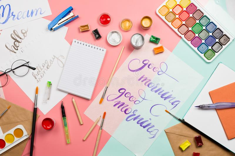 Beautiful flatlay arrangement with watercolors, brushes, glasses, brushpen, paints with good morning handlettering and other stati. Onary and art supplies royalty free stock images