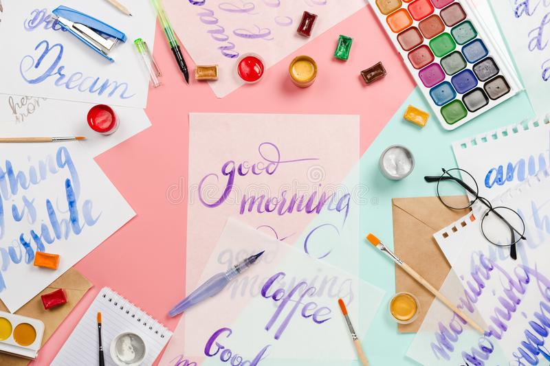 Beautiful flatlay arrangement with watercolors, brushes, glasses, brushpen, paints with good morning handlettering and other stati. Onary and art supplies royalty free stock photos