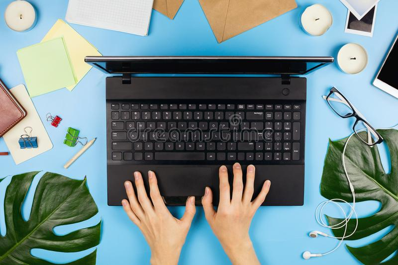 Beautiful flatlay with woman`s hands printing, a laptop, mobile phone, glasses, philodendron leaves and other accessories. Beautiful flatlay with woman`s hands royalty free stock photography