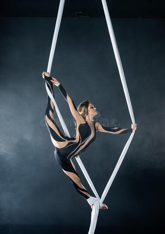 Beautiful flexible woman gymnast with white aerial silks isolated on black stock image