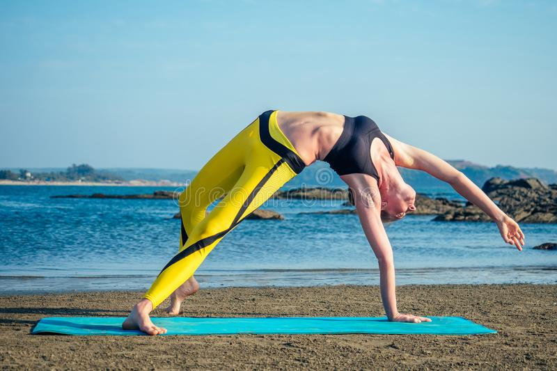 Beautiful and flexible woman-striker practicing yoga and doing stretching exercises for the beach royalty free stock image