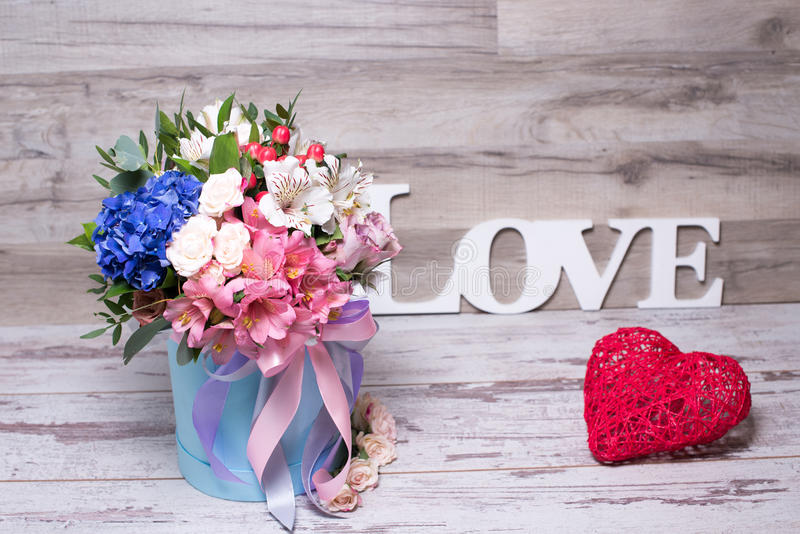 Beautiful floral arrangement in hat box with the inscription LOVE and action figure heart , shabby white wooden table stock photos