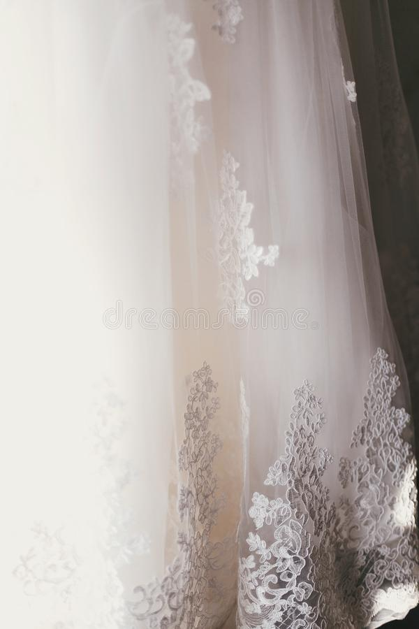 Beautiful floral detail on silk wedding dress. lace ornament on. White gown, bridal morning preparations stock photos