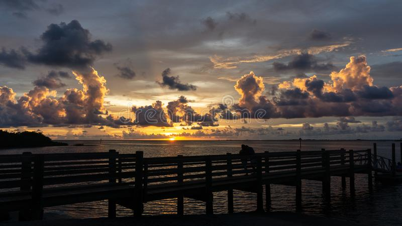 Beautiful Florida Gulf Coast sunset. A couple in silhouette unidentifiable watches a beautiful Florida Gulf Coast sunset from a pier at Fort Island Beach, a royalty free stock photography