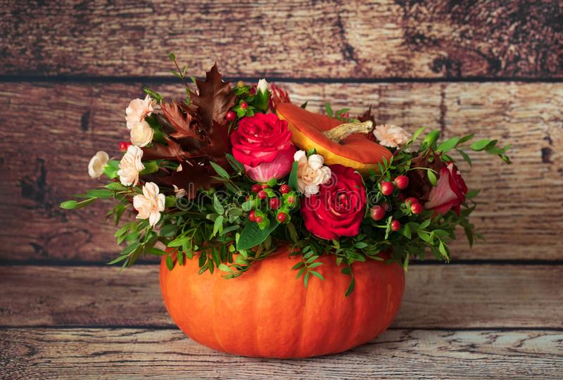 Beautiful flower arrangement in a pumpkin. Autumn floral pumpkin background. Pumpkin with flowers on a wooden background. Autumn stock photo