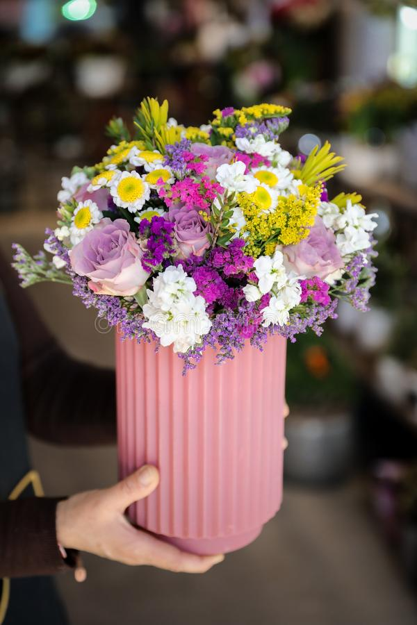 Beautiful flower arrangement with roses, limonium sinuatum, chrysanthemum flowers and other plants in the woman florist hands stock photos