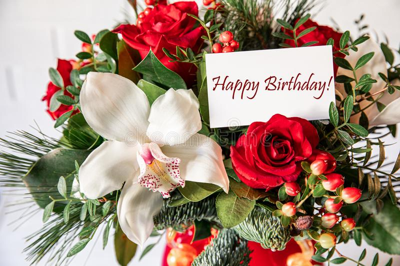 Beautiful flower arrangement of white orchid, red roses, natural spruce branches with card text Happy Birthday stock photos