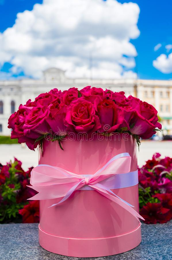 Beautiful flower bouquet of pink roses in big round pink hat box. royalty free stock image