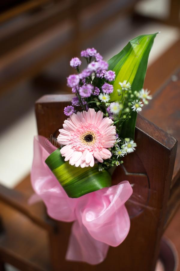 Flower Decoration for Wedding. Beautiful flower decoration with ribbon used in church pew for a wedding mass stock images