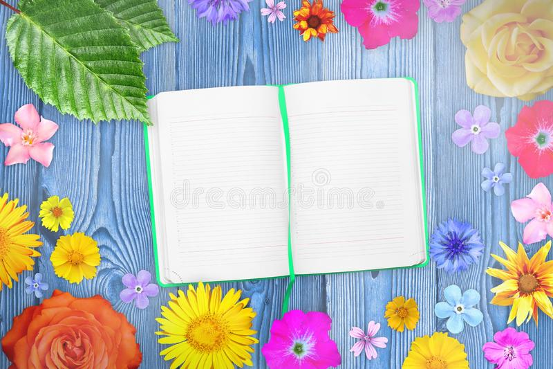 Beautiful flower frame with notebook in center on purple wooden planks background. Floral composition of spring or summer flowers. royalty free stock photography