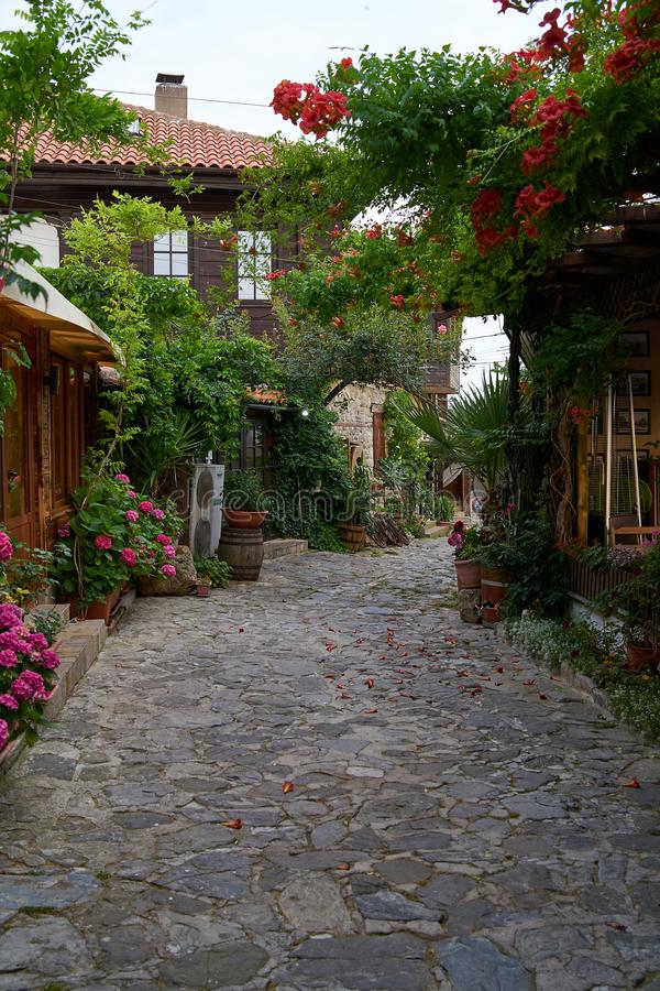 Beautiful flower and narrow street with restaurants and cafes of the ancient seaside town. stock photography
