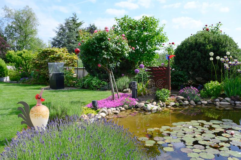 Beautiful flowerbeds in garden around pond royalty free stock photography