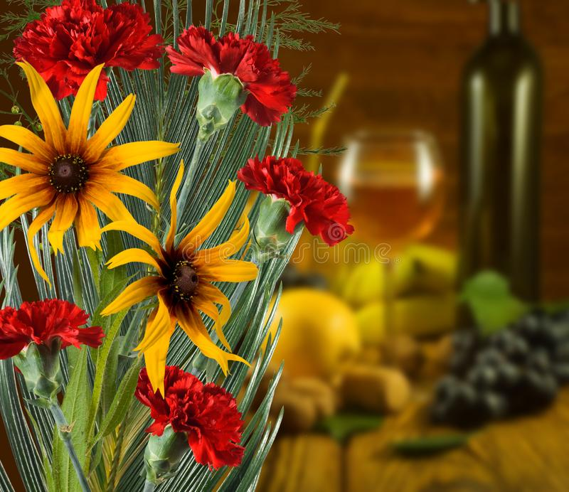 Beautiful flowers against the glass with wine and fruit background royalty free stock photography