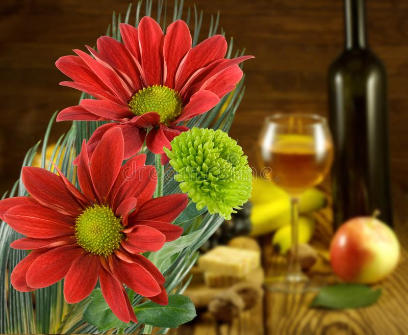 Beautiful flowers against the glass with wine and fruit background stock photography