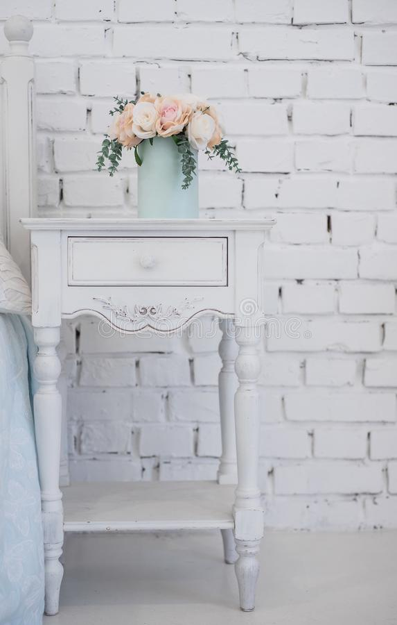 Beautiful flowers in a box of soft blue color and stand on a carved wooden pedestal. the interior in the room girls royalty free stock image