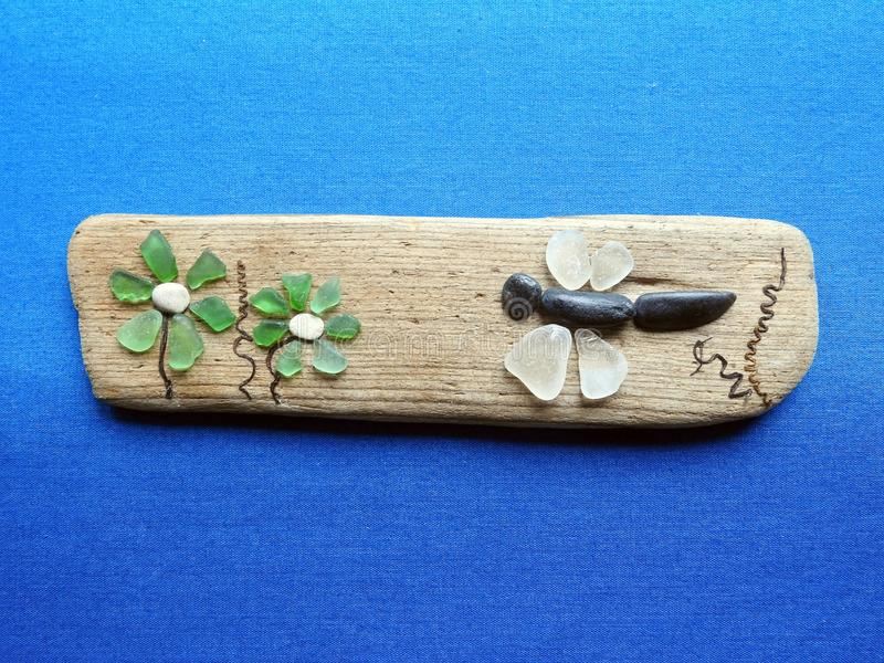 Beautiful flowers and dragonfly made from natural sea glass and sea wood, Lithuania stock images