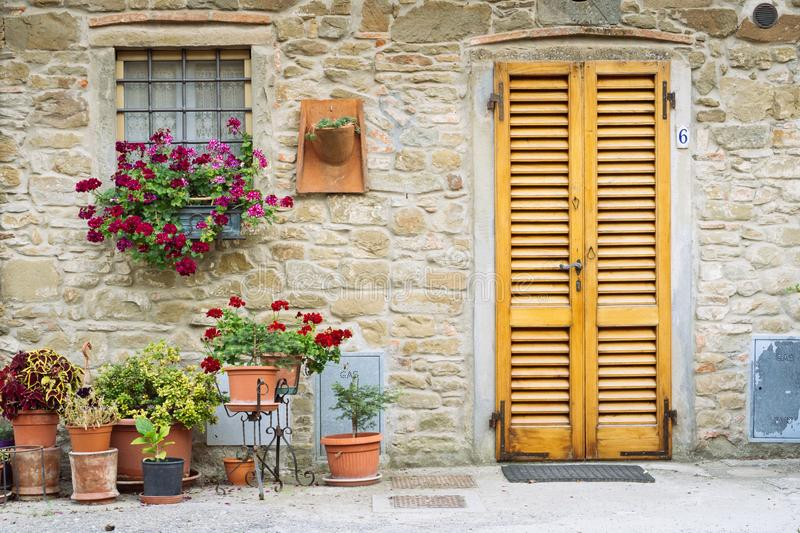Beautiful flowers in front of stone wall in a small village of medieval origin. Volpaia, Tuscany, Italy. Beautiful flowers in front of stone wall in a village of stock photos