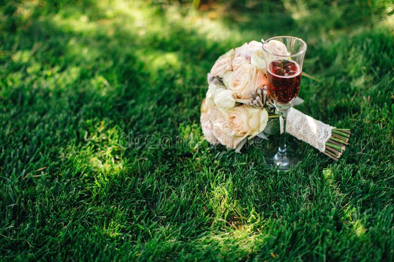 Our beautiful wedding. Beautiful flowers lie on the green grass and pink champagne stock image