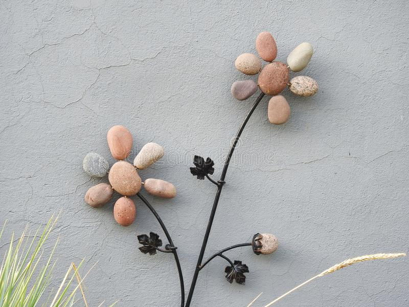 Flowers made from stone on home wall, Lithuania stock image