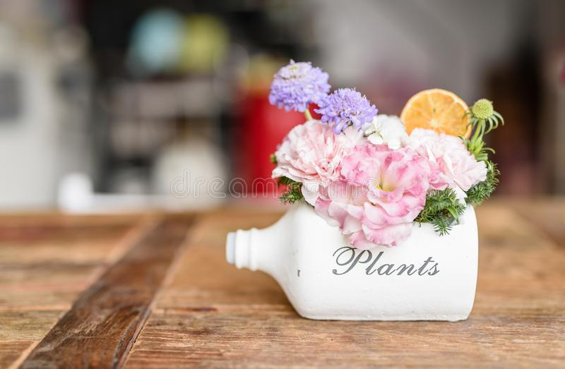 Beautiful flowers and tree potted in white bottle pot stock image