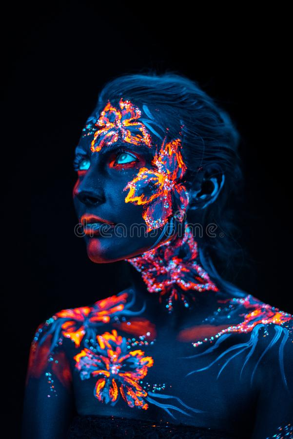 Beautiful flowers in UV light on a young girl face and body stock image