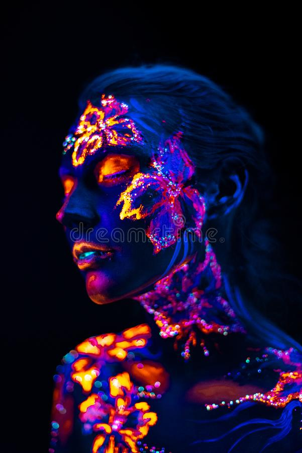 Beautiful flowers in UV light on a young girl face and body royalty free stock photos