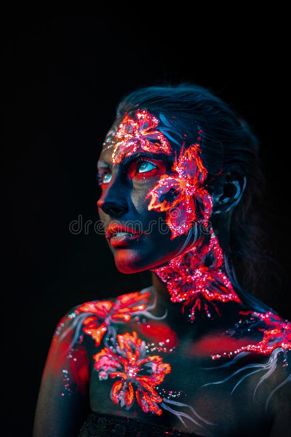 Beautiful flowers in UV light on a young girl face and body stock images